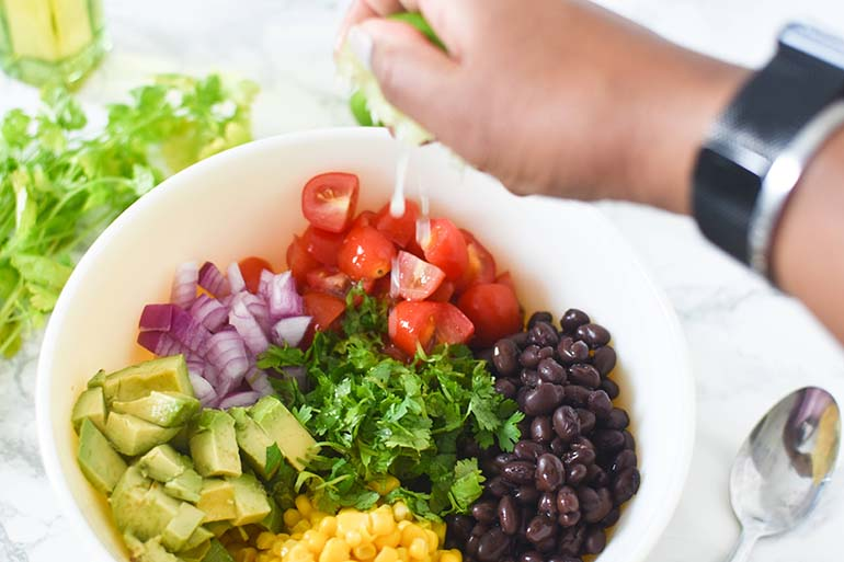 Avocado Black Bean Corn Salad in large bowl. Brown hand squeezing lime overtop
