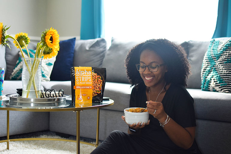 Black woman in living room with bowl of Vegan Southern Chicken and Rice